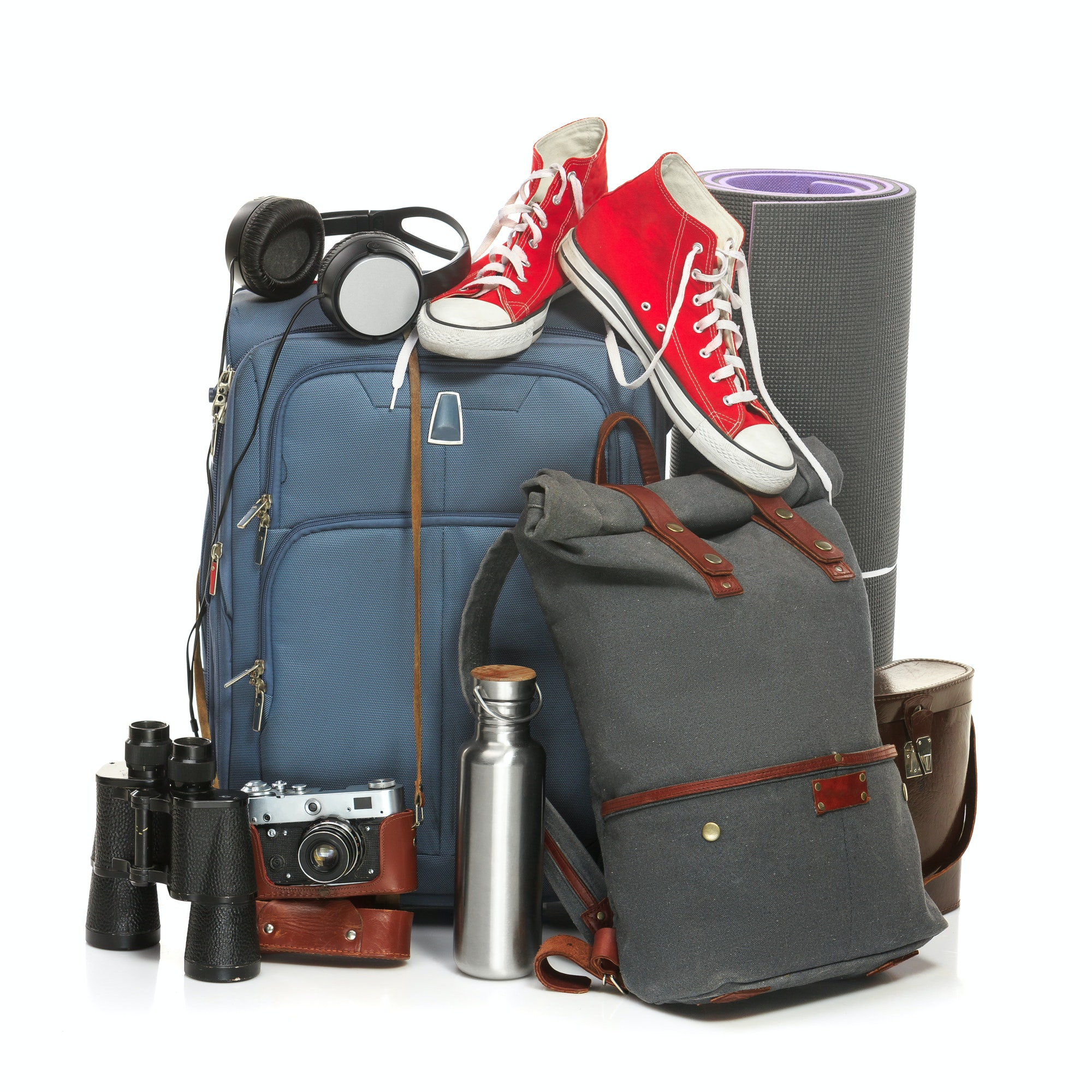 The suitcases, sneakers, retro camera, karrimat and binoculars on white background.